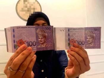 Nurul Nabihah menunjukkan perbandingan not kertas RM100 palsu diterima (kanan) dengan wang RM100 tulen.