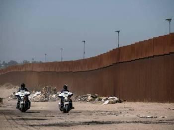 Pasukan keselamatan Mexico meronda di sekitar tembok sempadan AS-Mexico di Tijuana Baja. - Foto AFP