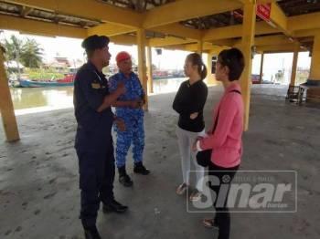 Penolong Pegawai Pangkalan Hadapan, Asharudin Che Ani (kiri) dan anggota APM Yan, Lans Koperal Mohd Nor Ismail (dua,kiri) berbual dengan Shwu Yi (dua kanan) dan Ghik Leng (kanan) di Jeti LKIM Kuala Sala, di sini, hari ini.
