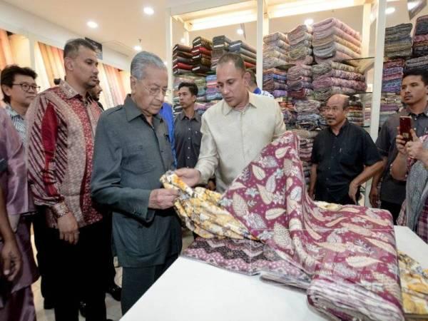 Dr Mahathir (dua dari kiri) melihat fabrik yang dijual di Jakel Langkawi sambil dibantu Mohamed Faroz.
