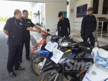 Mohd Ismail (kiri) melihat motosikal yang dirampas pada 4 Disember lalu.