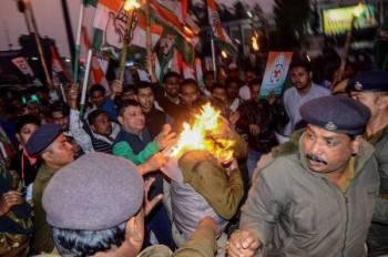 Beberapa anggota polis cuba menyelamatkan rakan sepasukannya yang terbakar semasa protes membantah CAB di Tripura semalam. - Foto AFP