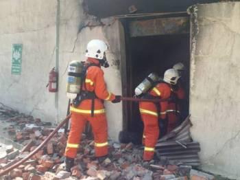 Anggota bomba sedang memadamkan kebakaran di sebuah kilang pemprosesan ayam terbesar di Seri Kesang, Jasin di sini hari ini.