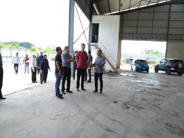 Kok Yew (dua dari kiri) dan Tze Min (dua dari kanan) ketika turun memeriksa kilang tanpa kebenaran pada Selasa lalu di Taman Songket Indah, dekat sini yang didapati sudah dikosongkan. -Foto Facebook Ooi Tze Min