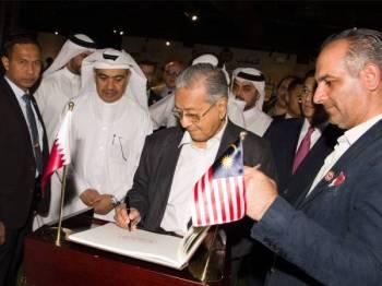 Dr Mahathir (tengah) menandatangani buku lawatan ketika hadir melawat Ladang Baladna hari ini. Turut kelihatan, Menteri Perdagangan dan Industri Qatar Ali Ahmed Al Kuwari (dua,kiri). -Foto Bernama