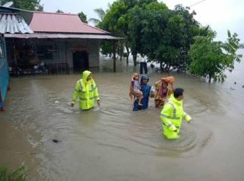 Anggota bomba dan polis memindahkan mangsa banjir selepas dua kampung di daerah Rompin dinaiki air petang tadi. FOTO: Ihsan bomba