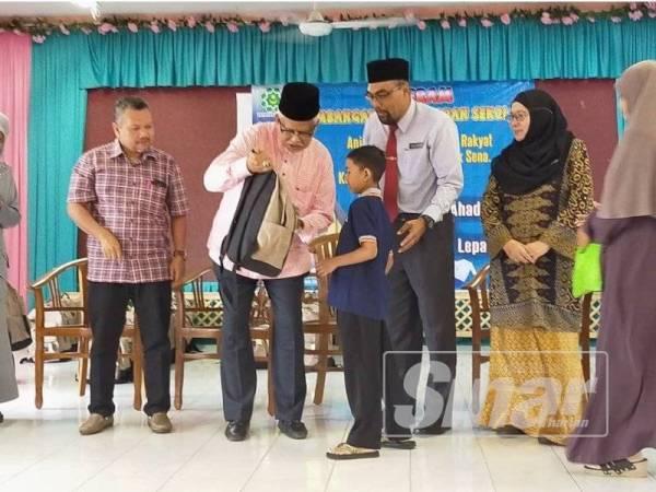 Mahfuz (dua dari kiri) menyampaikan kelengkapan sekolah kepada pelajar yang terpilih di Sekolah Kebangsaan Haji Abu Bakar, Lepai Bukit Pinang di sini hari ini.