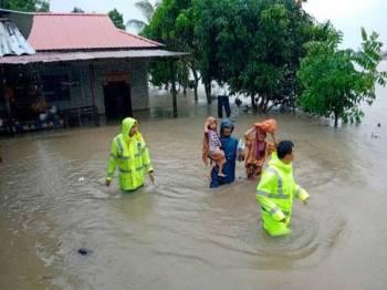 Penduduk kampung di Rompin diiringi anggota keselamatan berpindah selepas kampung mereka dinaiki air banjir semalam. Foto: Bernama