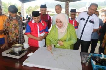 Shahaniza mencanting batik sambil diperhatikan Mohd Ariffin (dua dari kiri) sempena perasmian mesyuarat pertama pertubuhan tersebut di Lanab Qalbu Maran.
