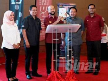 Mukhriz (tengah) menunjukkan buku Direktori Pelancongan Negeri Kedah yang dilancarkan sambil disaksikan Uzaidi (dua dari kiri) ketika gimik pelancaran hari ini.