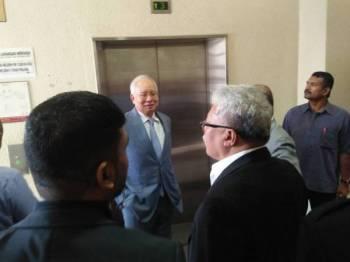 Najib (tengah) ketika berada di luar mahkamah selepas prosiding bela diri dalam kes skandal SRC International Sdn Bhd di Mahkamah Tinggi Kuala Lumpur hari ini.