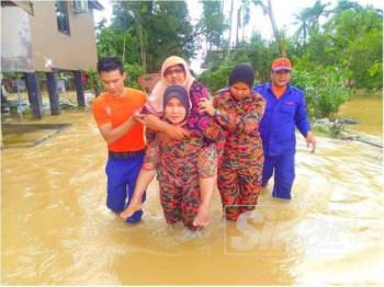 Dua pegawai JBPM Kelantan bergilir-gilir menggendong seorang warga emas sejauh 100m meredah banjir sedalam 0.5 meter di Kampung Banggol Kulim.