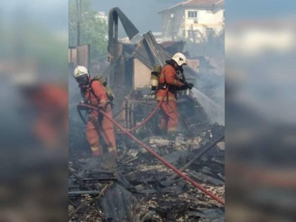 Anggota bomba membantu memadamkan kebakaran melibatkan sederet rumah setinggan di Kampung Kovil Hilir di sini petang tadi.