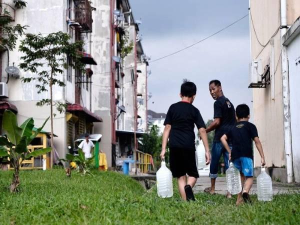Nazli Baharuddin Osman (tengah) bersama dua anak saudaranya Zikir Helmi (kanan) dan Muhammad Akil Muhammad Diah (kiri) mengangkat botol air yang ditadah daripada 12 paip air yang disediakan oleh pihak Pengurusan Air Selangor Sdn Bhd (Air Selangor) di tepi Jalan 4/2 Seksyen 4 Bandar Baru Bangi untuk dibawa ke rumah mereka di Pangsapuri Jubli Perak berikutan gangguan bekalan air yang berlaku di sekitar kawasan tersebut. - Foto Bernama