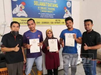 Noridzuan (kiri) bersama pengusaha premis penyembelihan ayam di Pasar Jerantut yang dianugerahkan Sijil Halal Malaysia kelmarin.