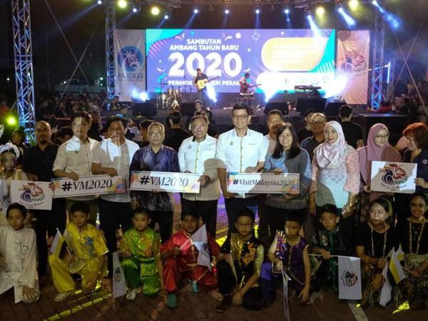 Kar Hing (belakang, tengah) bergambar bersama pengunjung yang hadir meraikan sambutan Tahun Baharu 2020 di Dataran Maritim malam tadi. - Foto Bernama