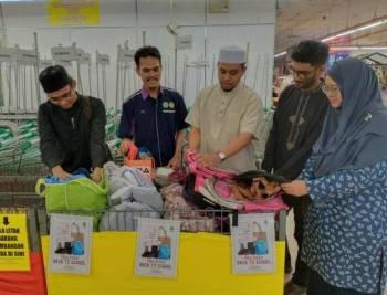 Amir (tengah) melihat barangan keperluan sekolah yang dikumpulkan di kaunter yang tertulis 'Preloved Back To School' di Pasaraya Econsave Bandar Puteri Jaya Sungai Petani.
