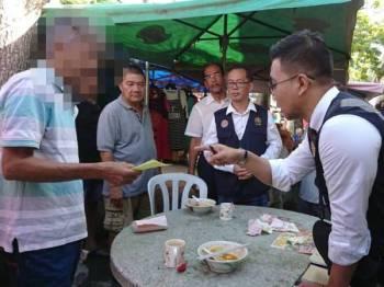 Lelaki berusia 50-an yang panas hati apabila diberikan notis kompaun ketika operasi penguatkuasaan di tempat makan dilarang merokok yang diketuai Exco Kesihatan dan Anti Dadah, Low Chee Leong di Bukit Baru, di sini, hari ini.