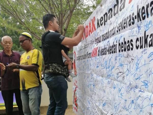 Orang ramai turut menurunkan tandatangan sebagai membantah penjualan minuman keras bebas cukai di Pulau Pangkor pada 29 Disember lalu.