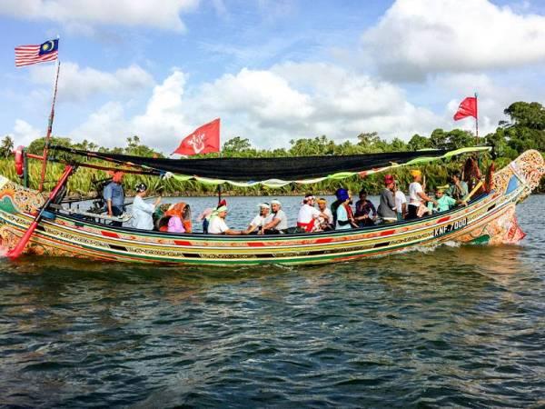 Seramai 40 ahli Persatuan Pencinta Busana Negeri Kelantan mencipta kelainan dengan mengenakan busana tradisi Melayu seperti zaman dahulu kala menyusuri Sungai Pengkalan Datu dengan menaiki Perahu Kolek sejauh enam kilometer di sini hari ini. - Foto: Bernama