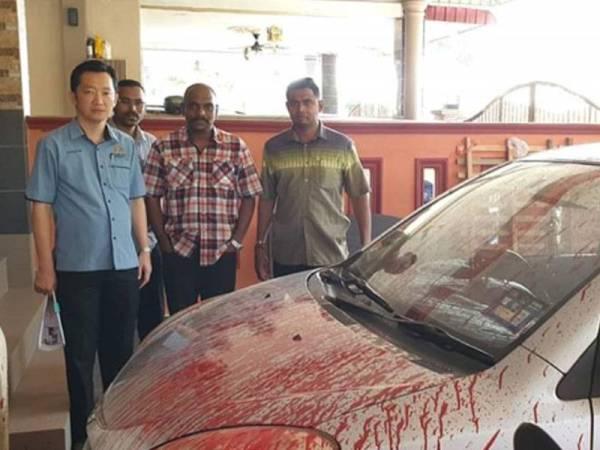 Cha Kee Chin (kiri) dan Senthivelu (dua dari kanan) melihat keadaan kereta Myvi yang disimbah dengan cat merah. - Foto sumber Facebook Cha Kee Chin