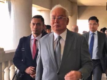 Najib kelihatan keluar dari bilik Mahkamah Tinggi Jenayah 3 selepas memberi keterangan bagi prosiding membela diri terhadap pertuduhan berhubung dana SRC International Sdn Bhd hari ini.