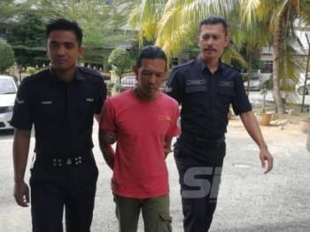 Tertuduh ketika dibawa anggota polis ke Mahkamah Majistret Tampin hari ini.