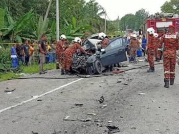 Anggota bomba membantu mengeluarkan mayat tiga beranak yang tersepit dalam kemalangan di KM145 Jalan Kuala Lumpur-Kuantan hari ini. - Foto JBPM