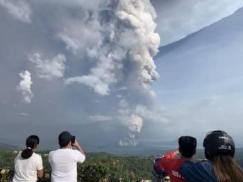 Penduduk mengambil gambar letusan gunung berapi Taal yang dilihat dari bandar Tagaytay di wilayah Cavite dekat barat daya Manila. - Foto AFP