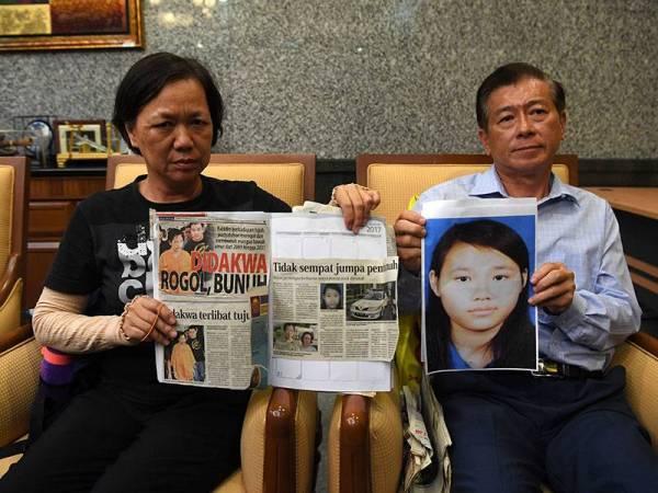 Siew Lin bersama suami, Sew Kok Wee menunjukkan keratan akhbar mengenai pembunuhan anak mereka, Annie Kok Yin Cheng. - Foto Bernama