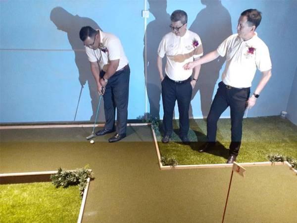 Amirudin (kiri) mencuba permainan golf di fasiliti yang disediakan di kediaman pangsapuri di BSP21.