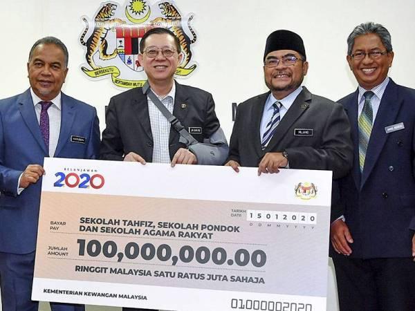 Lim Guan Eng menyerahkan cek bernilai RM100 juta kepada Dr Mujahid (dua, kanan) pada Majlis Penyerahan Cek RM100 juta Untuk Sekolah Tahfiz, Sekolah Pondok dan Sekolah Agama Rakyat di Kementerian Kewangan hari ini. -Foto Bernama