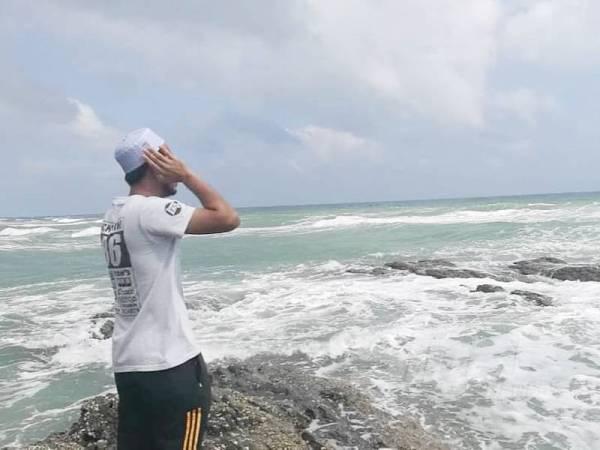 Salah seorang ahli keluarga melaungkan azan sebagai ikhtiar dalam usaha pencarian empat pelajar PSMZA yang dikhuatiri lemas di Pantai Teluk Bidara.