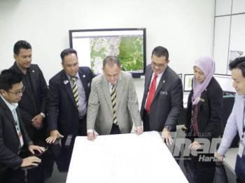 Mohamed Zin (tengah) melihat pelan Hutan Simpanan Kekal negeri Perak di bilik 'War Room' Jabatan Perhutanan negeri.