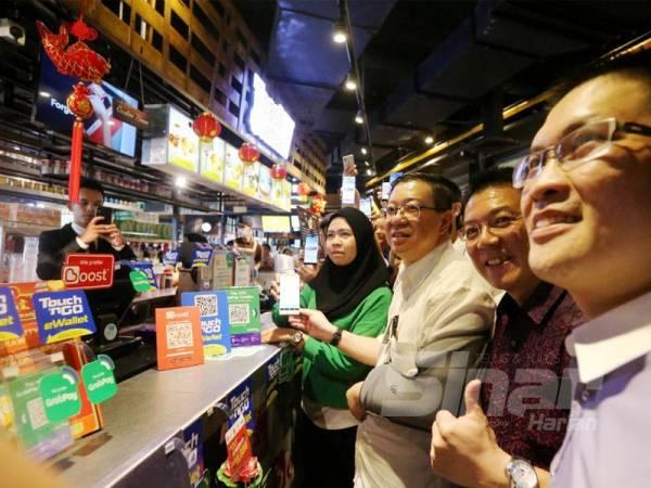 Guan Eng (tiga dari kanan) ketika meninjau Village Food Court di AEON Kinta City sempena pelancaran Inisiatif e-Tunai Rakyat hari ini.