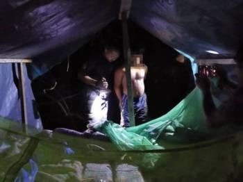 Anggota penguat kuasa melakukan pemeriksaan terhadap seorang warga Bangladesh yang ditahan bersembunyi di dalam bangsal. - Foto Jabatan Imigresen Terengganu