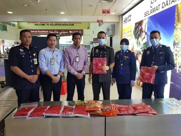Pegawai Maqis menunjukkan barang dirampas daripada penumpang yang tiba dari Singapura, kelmarin.