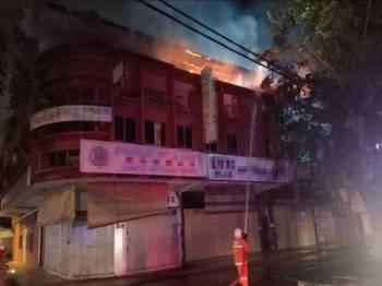 Anggota bomba memadam kebakaran di bangunan rumah kedai di Jalan Bukit Ubi, awal pagi tadi. - Foto ihsan bomba
