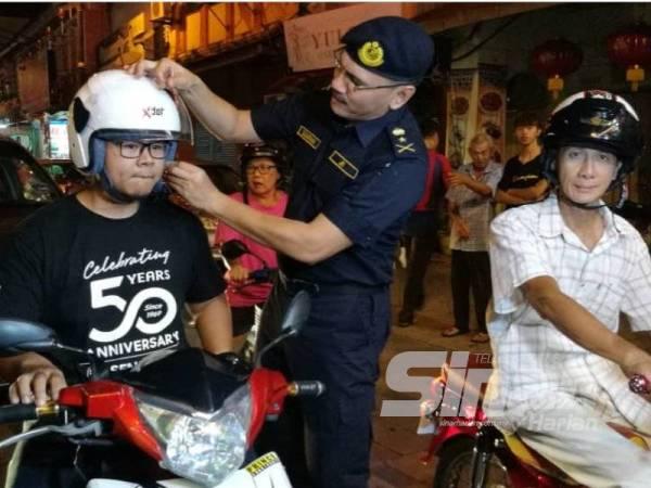 Zulkarnain memakaikan topi keledar yang diberikan kepada salah seorang pengguna jalan raya di Jalan Kampung Cina di sini sempena pelancaran Ops Tahun Baru Cina 2020 Peringkat JPJ Terengganu malam tadi.