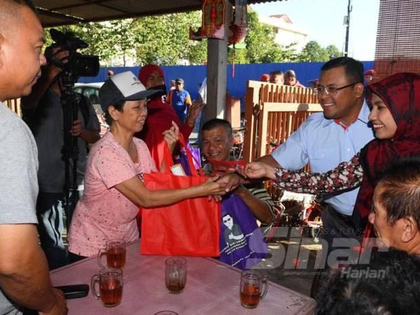 Amirudin (dua kanan) dan isteri, Masdiana Muhamad (kanan) menyantuni masyarakat Tiong Hua di Selayang Baru hari ini.