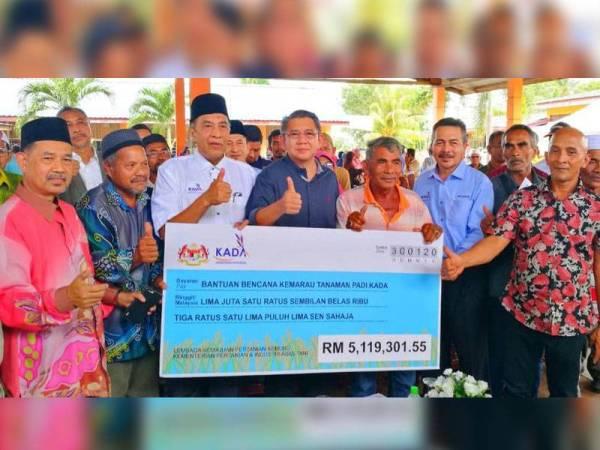 Salahuddin (empat dari kiri) dan Husam (tiga dari kiri) menyampaikan replika cek berjumlah RM5.119 juta kepada petani yang terjejas pada musim kemarau di PPK Cherang Rotan di sini hari ini.