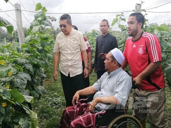 Salahuddin (kiri) meninjau tapak tanaman sayuran fertigasi yang diusahakan Zuliadin (tengah) di Kampung Rusila, Marang kelmarin.