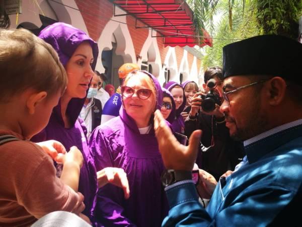 Mujahid (kanan) beramah mesra dengan pelancong selepas mengagihkan pembersih tangan percuma di Masjid Jamek Sultan Abdul Samad di sini hari ini.