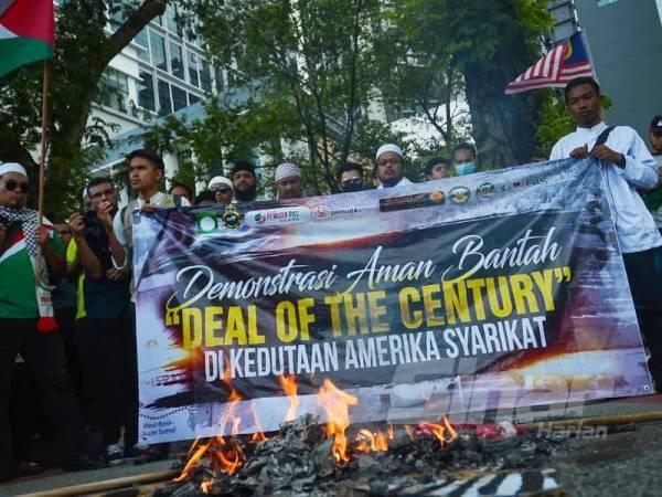 Patung Trump bersama bendera Amerika Syarikat dan Israel dibakar pada Himpunan Aman Bantah Deal of The Century di hadapan Kedutaan Amerika Syarikat hari ini. - Foto SHARIFUDIN ABDUL RAHIM