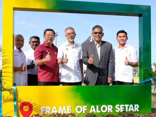 Raja Kamarul Bahrin (tiga dari kanan) dan Kok Yew (tiga dari kiri) merakamkan kenangan di bingkai gambar gergasi 'Frame Of Alor Setar' di Dataran Medan Bandar sebelum perasmian program jalinan kerjasama 'let's do it right' hari ini.
