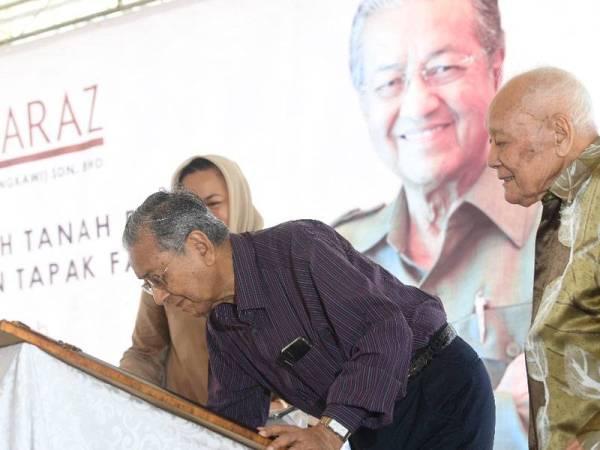 """Tun Mahathir menurunkan tandatangan sebagai simbolik Majlis Pecah Tanah Fasa 2: """"Villa Sirehan"""" di Padang Gaong, Mukim Ulu Melaka, hari ini."""