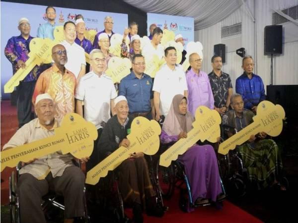Azmin (berdiri, empat dari kanan) bergambar bersama pimpinan kerajaan, wakil Eco World dan sebahagian peneroka pada Majlis Penyerahan Kunci Rumah Laman Haris kepada Peneroka Rancangan Revolusi Hijau Peringkat 2 dan 3 Mukim Ijok di sini hari ini.