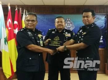 Roslee (tengah) menyaksikan Majlis Serah Terima Tugas Ketua JSJK Terengganu daripada Ketua JSJK Terengganu, Superintendan Mohd Rawi Ab Ghani (kiri) kepada Timbalannya Deputi Superintendan Hamdan Zali (kanan).