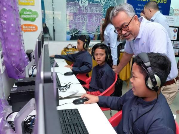 Idham beramah mesra dengan kanak-kanak yang menggunakan perkhimatan internet di Pusat Internet Kampung Telipok, Sabah.