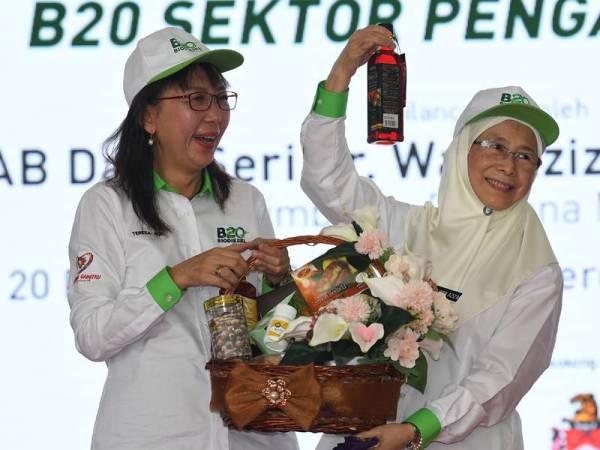 Dr Wan Azizah (kanan) menerima cenderahati daripada Teresa pada Pelancaran Program Biodiesel B20 Sektor Pengangkutan di Dataran Merdeka hari ini. - Foto Bernama